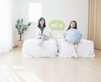二人の娘が同じ子供部屋のそれぞれのベッドの上にいる