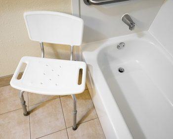 シャワーチェアが老人でも入りやすそうな段差が低い浴槽の近くにおいてある