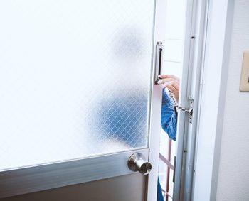 泥棒が部屋に侵入するためにドアのチェーンロックを外そうとしている