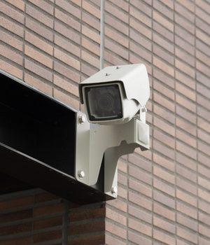 壁に取り付けられてこちらを向いている防犯カメラ