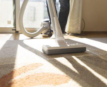リビングのカーペットを人が掃除機で掃除している
