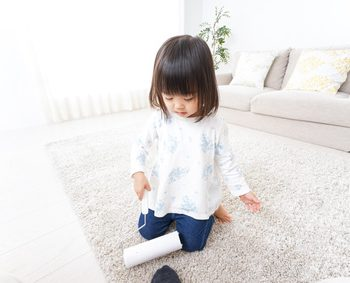 カーペットを掃除している小さな女の子