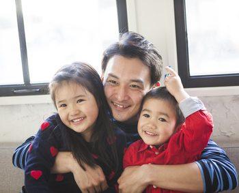 笑顔で二人の娘を抱きかかえるお父さん