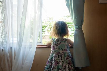 窓際に立って外をずっと見ている子供