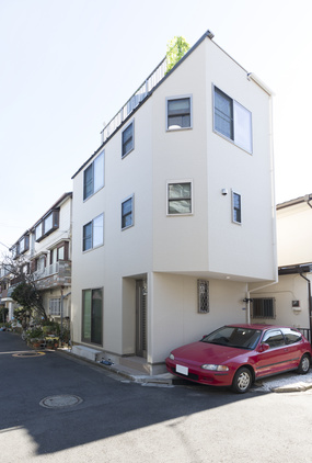 角に建つ木造3階建ての白い住宅