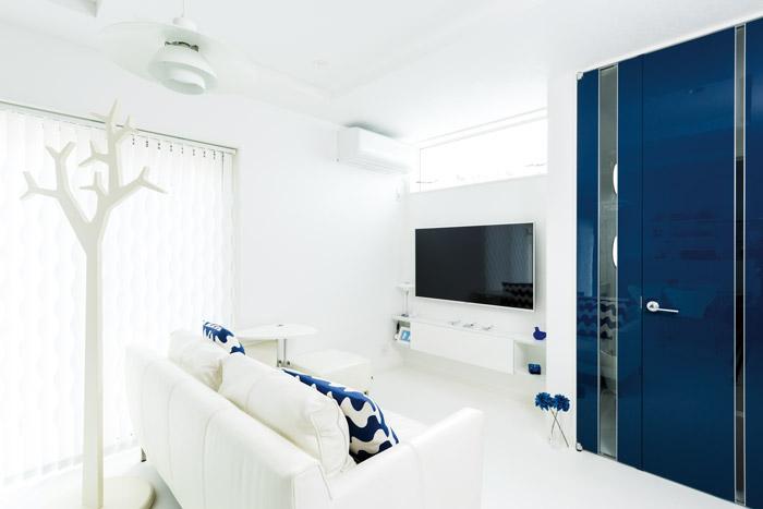 白と青のコントラストが鮮やかなリビングスペース。周囲と目の高さが合わない位置に設けた窓から自然の光が差し込み、空間を明るく包んでいます。住宅の密集した都市立地で、プライバシーへの配慮と明るい空間を両立させた設計です。