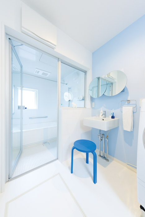 Mさま支給のデザイン鏡をあしらった、印象的な造作洗面。浴室の壁をガラス壁にすることで、視線が抜けて明るく開放的なサニタリースペースに仕上げました。