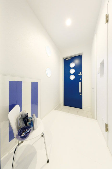 インパクトのあるブルーの扉を採用した近未来的なモダンデザインの玄関スペース。白と青のツートーンの空間に丸窓が並び、全体に統一性を持たせた仕上がりです。