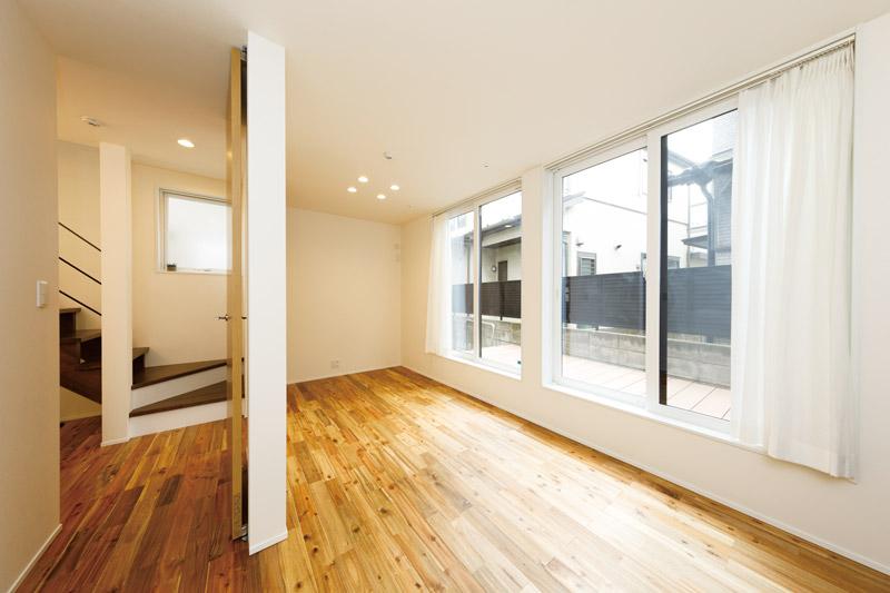 「置き家具で場所をとらずに、限られたスペースを広々と使いたかったのです」という室内は、的確な収納計画で驚くほどすっきり。天井高まで大きく開いたハイサッシが開放的なプライベートルームの床は、木目の鮮やかなアカシアの無垢材をあしらいました。窓外のデッキは窓枠に高さを合わせています。