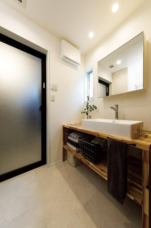 白を基調とした中に、木のぬくもりを活かした造作棚をしつらえたシンプルな洗面台。モノを置かずにコンパクトにまとめられていて、きれいに保たれています。明かり取りのスリット窓があることで閉塞感がなく、清涼感あふれる仕上がりです。