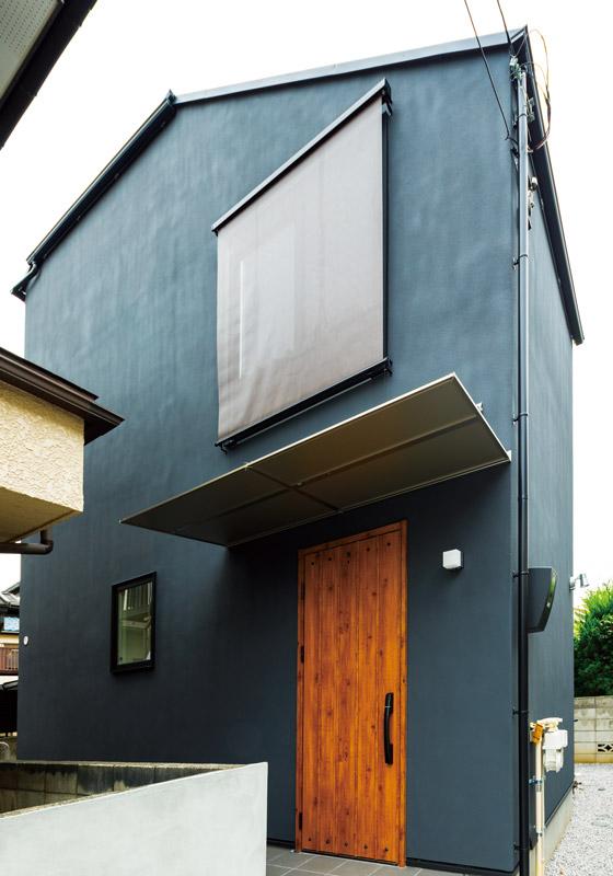 シックな外壁に木の玄関扉をアクセントにしたシンプルモダンな外観。ステンレスの玄関庇など質感の異なる素材を効果的にとり入れています。建物正面から見てもインパクトのある2階の大きな窓が印象的で、ロールカーテンで道路側からの視線もコントロールしています。