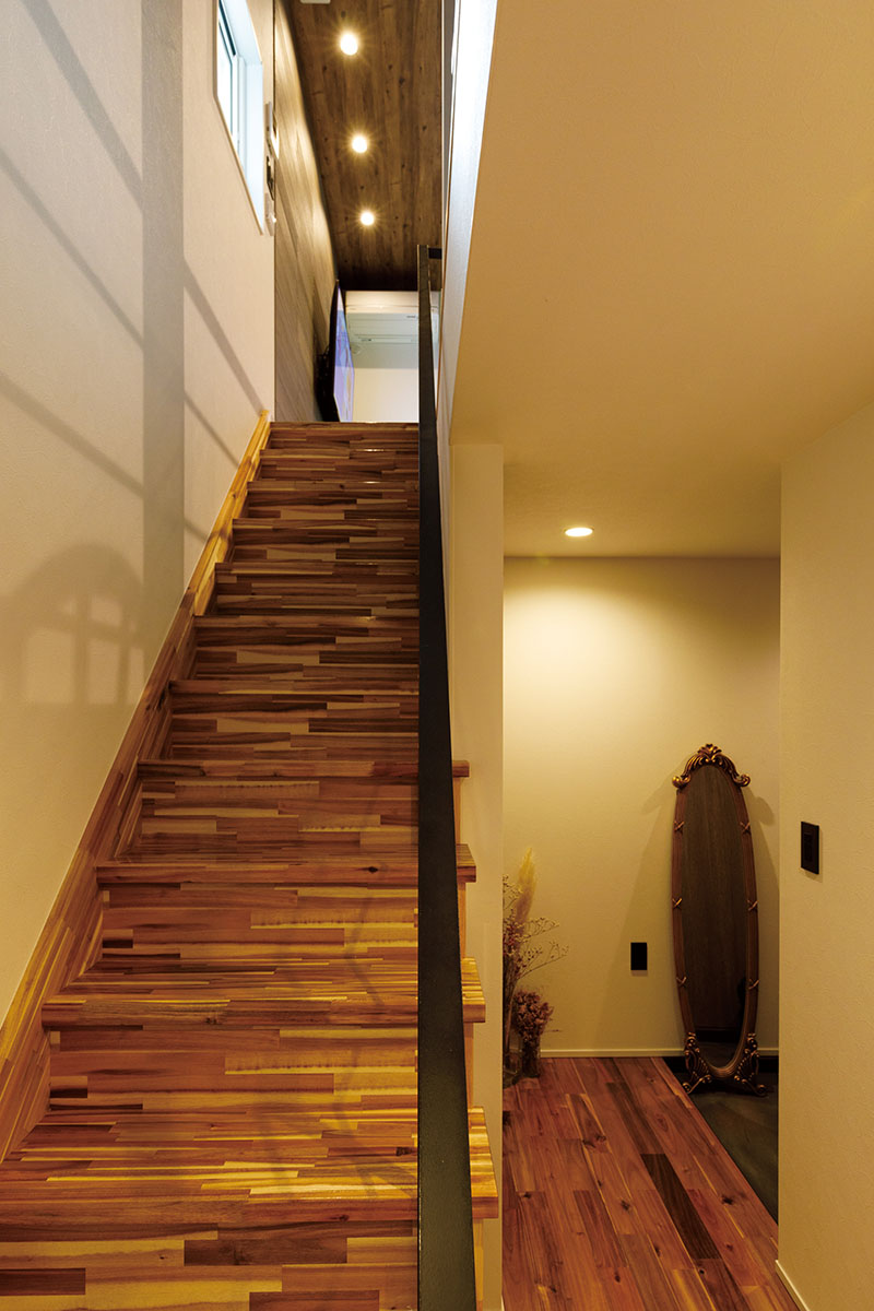 奥行きのある1階の階段ホール。木の質感あふれる階段は、手摺りをスチールにして、光を通すオープンなデザインに。コントラストの効いた、しっとりとした落ち着きのあるモダンな空間を演出しています。