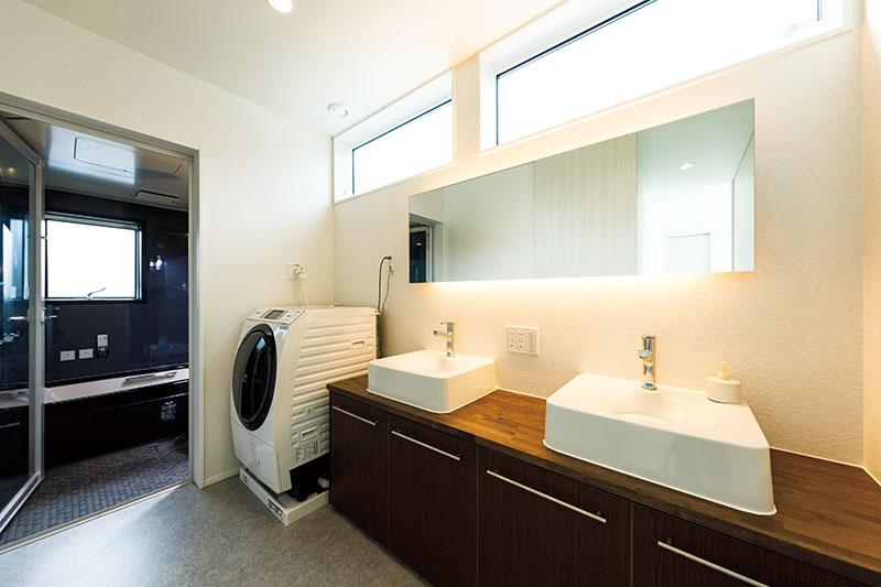 洗面台はホテルライクなツーボウル仕上げにしました。ワイドな高窓から光が差して朝は清々しく、夜はワイドミラーの間接照明でやわらかく、ムーディに。「リラックスタイムをくつろいで過ごせるように」(Oさま)と、浴室はシックで落ち着きのある色合いに仕上げました。