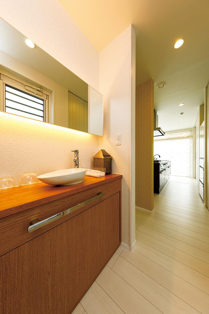 キッチンと直線的につながるパウダールーム(洗面室)。玄関やLDKとつながるオープンな設計は、ストレスなく自由に行き来することができます。LDKのあふれる光が奥まで届いて、明るく気持ちのよい空間です。