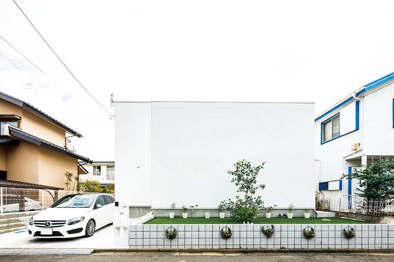 「街中の美術館をイメージしました」という外観は、シンプルモダンで洗練されたフラットルーフ。玄関の袖壁を高く立ち上げて大きな目隠しに。素材に光沢のあるミライアを使い、面を美しく見せています。前庭の緑とのコントラストが落ち着いた街並みに、美しく際立ちます。