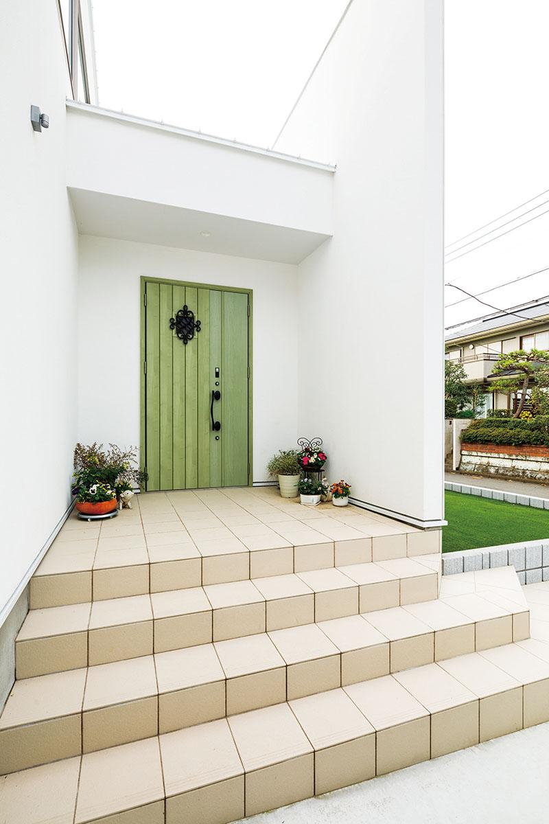 白亜の外観に組み合わせた爽やかなパステルグリーンの扉が印象的な玄関アプローチ。アイアンのハンドルや大きなオーナメントなど、「一つひとつの要素にこだわることで、自分たちだけの家をつくりたかったんです」と奥さま。幅のあるアプローチの階段が期待感を抱かせます。