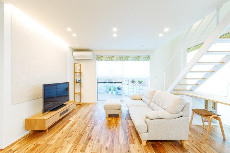アカシア無垢材のフローリングに木のTVボードやラック、生成り(きなり)のソファなど素材に統一感をもたせたインテリアでまとめています。奥のウッドデッキは室内とシームレスにつながるように、フロアと高さと揃えました。
