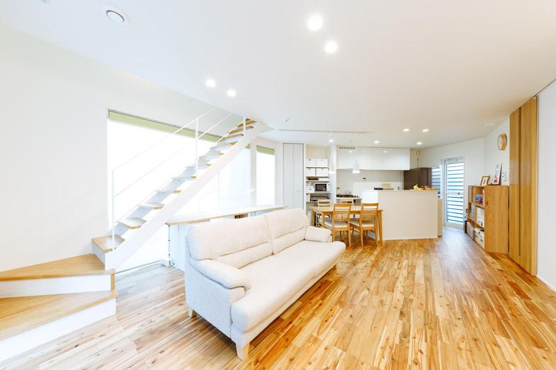 開放的で居心地の良いワンフロアのLDKに、家族のくつろぎの時間をデザインしました。住まいをつなぐリビング階段の向こうは、気持ちのいい一面の大開口。家族が互いの様子に気を配りながら、どこで何をしていても、明るく快適な時間を過ごすことができます。
