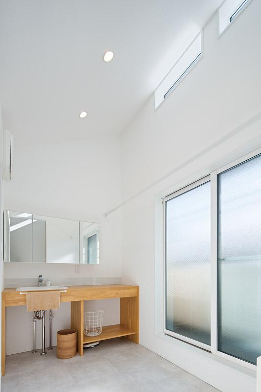 屋根の勾配を活かした天井の高い開放的なサニタリールーム。スリットの高窓から、やわらかな光が下りてくる清々しい空間に仕上げました。朝の光の入り方を考慮して、暮らしにすこやかなリズムを与えてくれる設計は、写真だけでは伝わらない心地よさを提供してくれる、建築家ならではの設計と言えます。