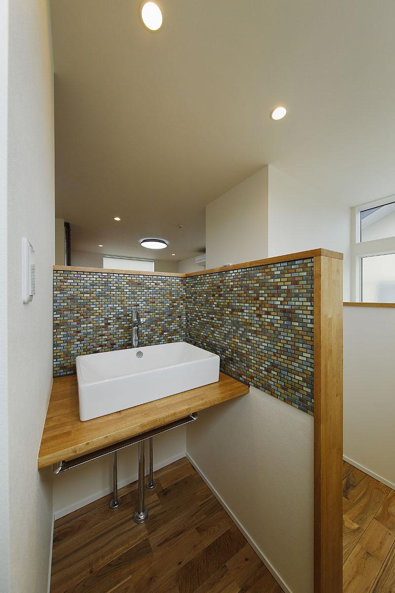 水回りのデザインもTさまのこだわり。洗面台は壁を手元までの高さにして、抜け感のある開放的な空間デザインに。細かなモザイクタイルをあしらいました。