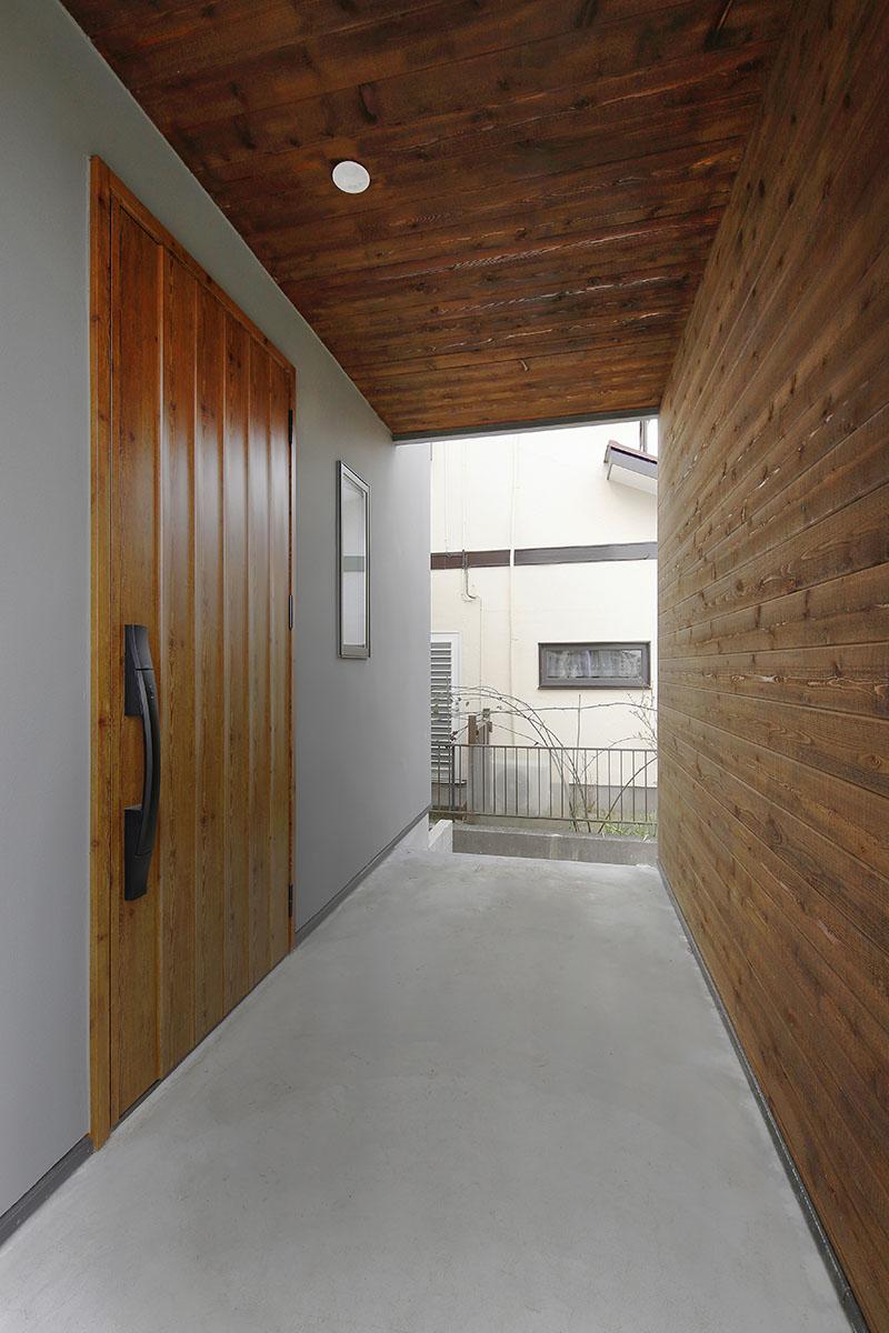 玄関アプローチは、雨風除けと共に道路側からの目隠しとしての役割も果たしています。天井と正面の壁には木材をあしらい、表情のある仕上がりに。自転車を並べておけるだけのゆとりのスペースを確保しました。