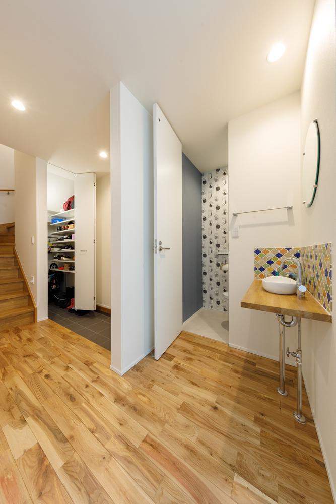 玄関から隠れるように、脇にトイレと洗面台を配置しました。トイレの壁紙は、1階と2階でデザインの違うクロスを使い、アクセントにしています。洗面台は鮮やかなタイル仕上げ、丸鏡をあしらって、おしゃれで楽しい空間に仕上げました。