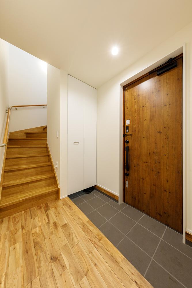 ご家族が並んで腰掛けられる幅の広い上がり框(あがりかまち)。玄関扉の重厚な質感が空間を引き立てます。階段下のスペースは、土間続きのシューズインクロークに活用しました。