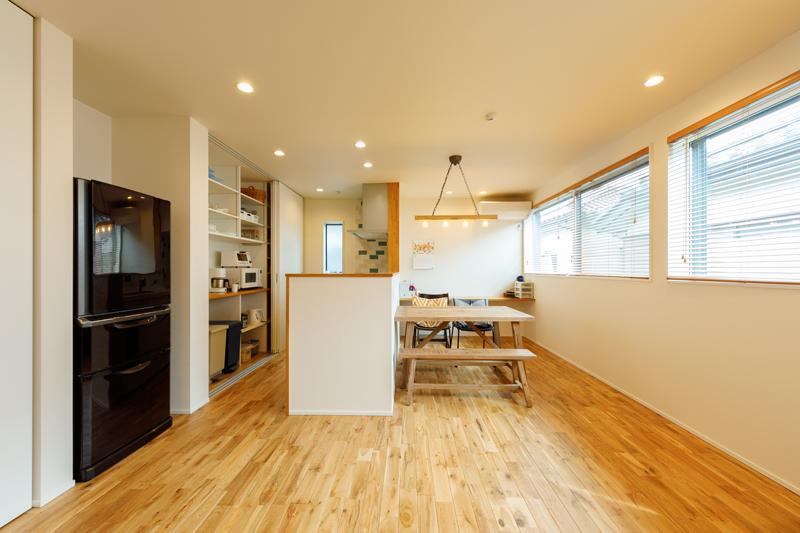 大きな窓を並べて彩光性を高めながら、近隣の住居と窓の位置や高さをずらすことで、周辺からの視線を気にすることなく、明るく心地よい暮らしを実現しています。キッチンは手元を隠すようにカウンターの高さを調節し、背面の収納はスライド扉を閉じるだけで空間をスッキリと見せることができます。