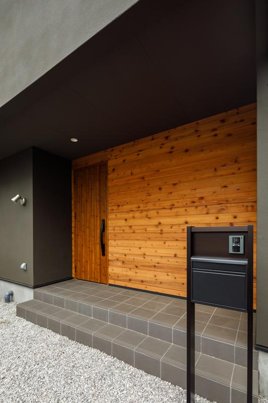 オーバーハングした玄関アプローチは自転車を並べておけるくらいのゆとりがあり、雨の日に玄関先へ雨が吹き込むのを防ぎます。玄関アプローチは仕上がりの統一感にこだわって、扉の質感に合わせて外壁の木材も厳選しました。