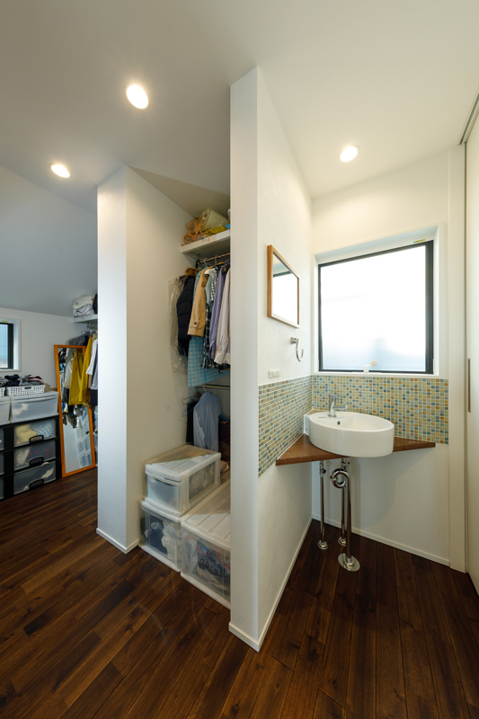 扉をつけず、ストレスのないフリーアクセスを実現した大容量のファミリークローゼット。お出かけの際の準備を手早く済ませられるように、一角に洗面スペースを設けました。