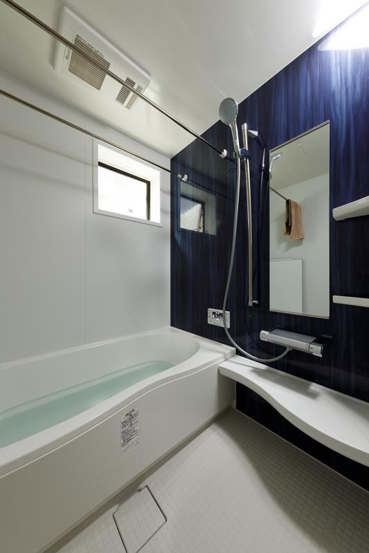 浴室の壁は、色の深いブルーに白のストライプが入った落ち着きのあるアクセントウォールに。換気窓からも自然光が届くことで、こもり感がやわらぎます。