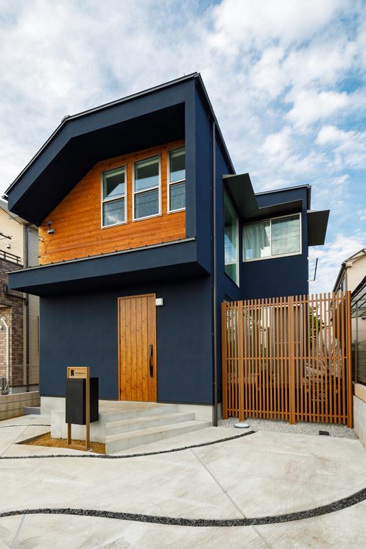 アクセントとして木の質感を組み合わせたネイビーの外壁、オーバーハングさせたような独特のフォルムが印象的な外観デザイン。内庭の向こうに開いた大きな窓や、曲線を取り入れたアプローチデザインも相まって、個性が際立つ仕上がりです。