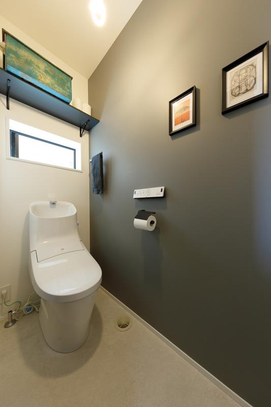 一面にグレーのアクセントクロスをあしらい、トイレはシックに仕上げました。換気・彩光の小窓から届く光が空間全体をやわらかく包みます。