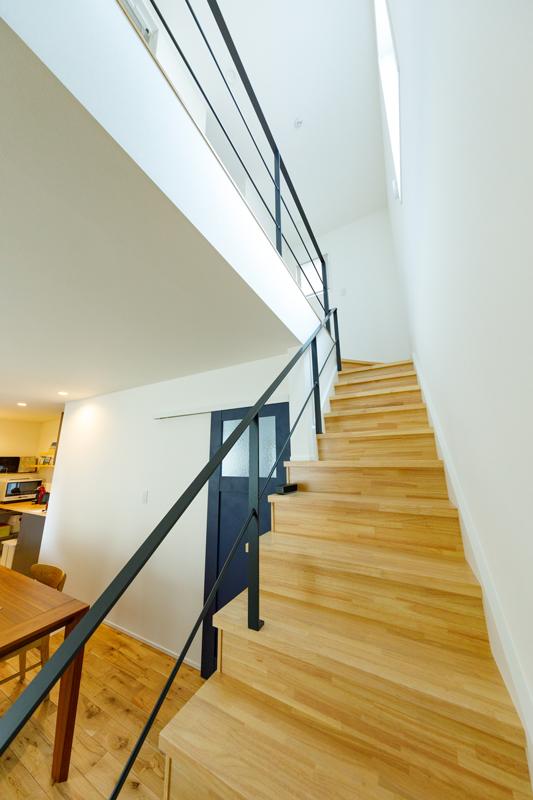 抜け感の心地いい階段室。階段の手すり部分はスチールのシースルーにして、上下階に光が通り抜けるようにしています。ほどよい陽だまりに、腰掛けて過ごしたくなる心地よさです。