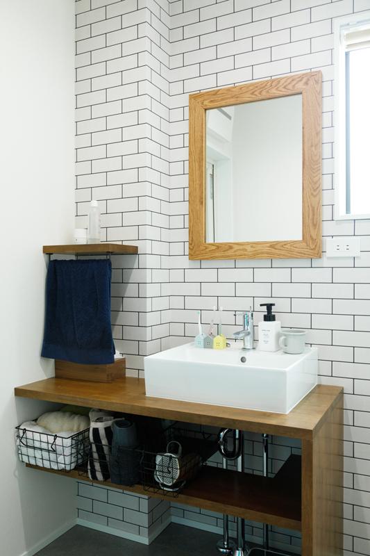 壁一面を清潔感のあるホワイトタイルのクロス仕上げにした洗面台。キャビネットは扉を付けずに、あえて見せることでスッキリとした印象に仕上がっています。使い勝手のいい高さに造作されたタオル掛け棚もポイントです。