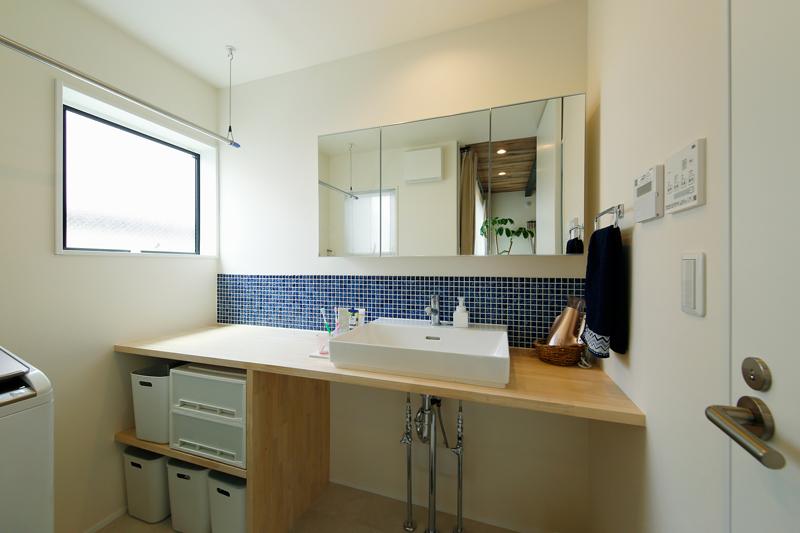 三面鏡の洗面台には木材とブルーのタイルを組み合わせ、すっきりとしたシンプルデザインに仕上げました。水回りの隣にはバルコニーがあり、洗う・干すの動線が短く、家事負担を減らす設計です。