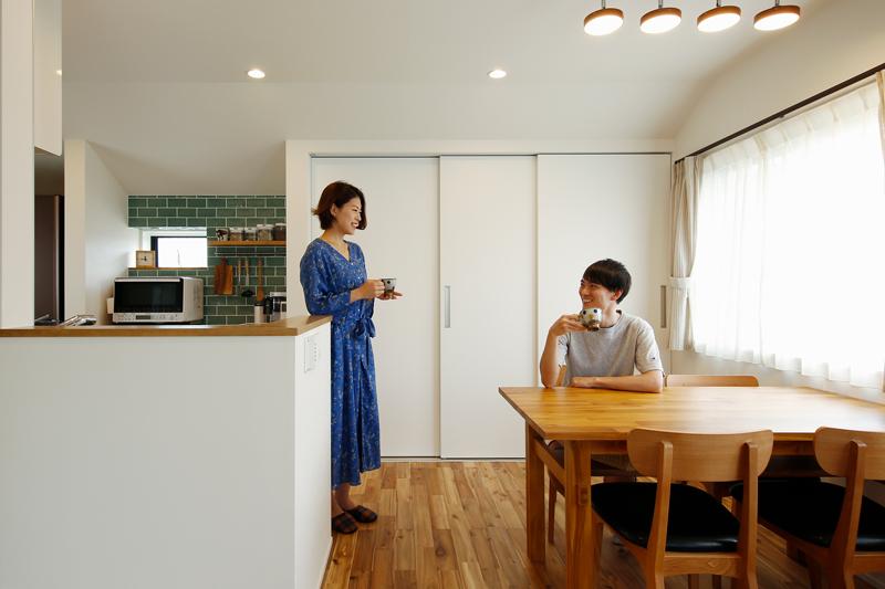 キッチンはリビング側から隠れるようにL字に配置しました。ダイニング周りのコンセントの位置は、使うシーンをイメージしながら高さまで計算して設計されています。リビング回りの品々は大容量の背面収納に格納して、すっきりと。