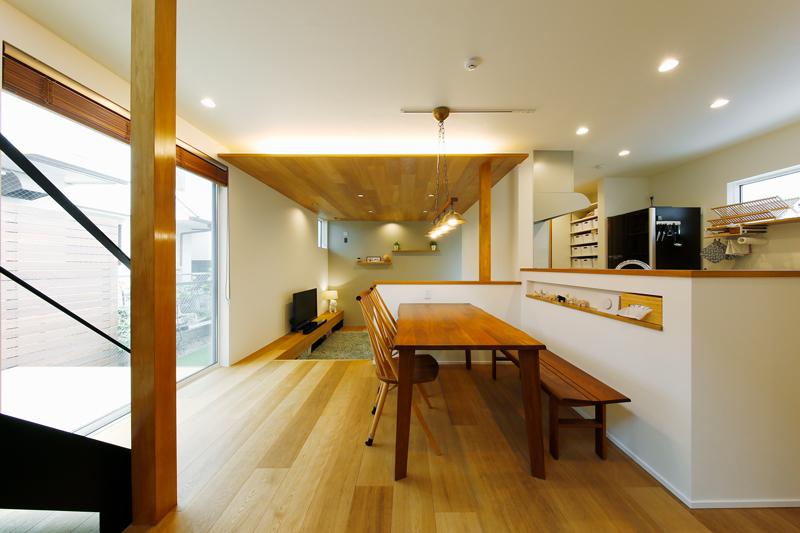 両サイドの開口部から光が差し込むダイニングキッチンは、奥のリビングと比べても明るさにメリハリのあるワンフロア設計です。フローリング材は幅の広いオークの合板にこだわりました。