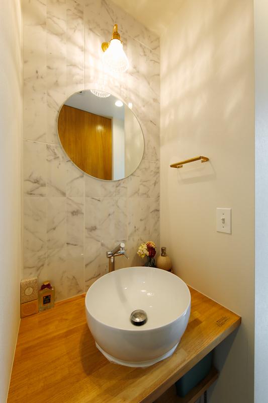 木のカウンターに小ぶりなラウンドの洗面ボウルをあしらい、丸鏡の背面壁は落ち着きのある大理石調で仕上げたホテルライクな洗面台。ニッチスペースにも、Iさまのデザインへのこだわりが感じられます。