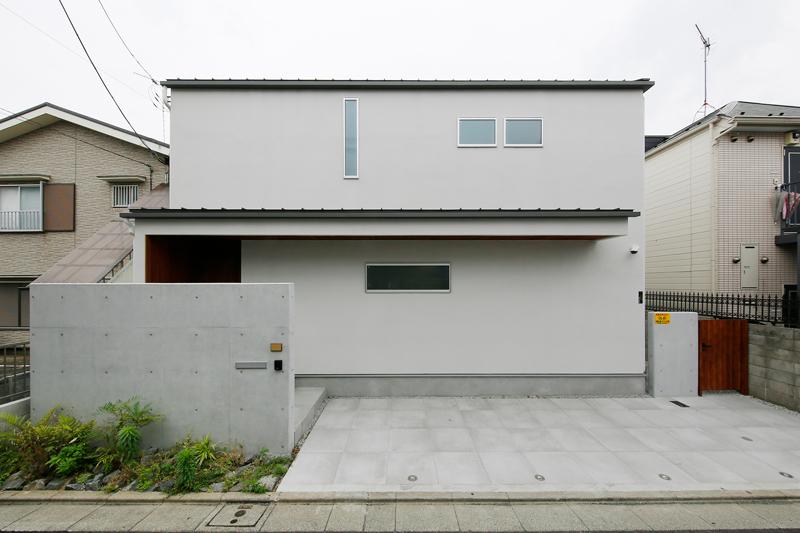 シンプルながら洗練された、安定感のあるスクエアな外観デザイン。プライバシーに配慮して高い位置に開口部をつくりました。アプローチに立ち上げた門壁は、玄関回りの目隠しや風除けの役割を果たしています。