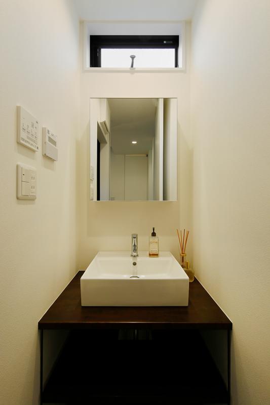 ホテルライクなシックモダンの洗面台。ニッチスペースながら高い位置に明かり窓をつけて清々しさ溢れる空間に仕上げました。