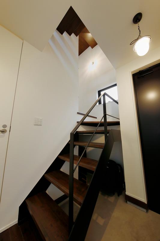 三鷹のモデルハウス見学で、奥さまが一目惚れしたという鉄骨のスケルトン階段。上階から溢れる光が壁に模様を描き出しています。階段下のスペースはモルタルの土間収納として活用しています。