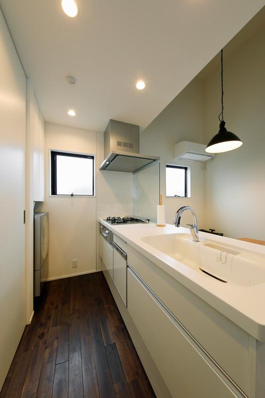 無垢床の深い色合いと対比を成すように、明るくやわらかなホワイトに包まれたオープンキッチン。家電や日用品は収納にしまって扉を閉め、すっきり美しい見た目に。