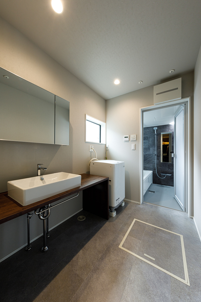 効果的に窓を配置して明るくすっきりと美しい洗面室。正面浴室もシックなアクセント壁にして、住まい全体のトーンに合わせました。洗面台もキャビネットなどをつくらず要素を少なくして、シンプルに仕上げています。