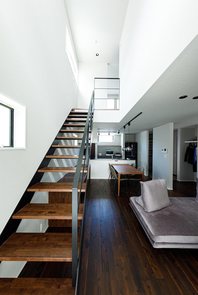 光の集まるリビング階段の吹き抜け。壁や天井の純白と、色が深く重厚感のある無垢床とのコントラストが効いて、空間全体を引き締めています。空間に溶け込むように、階段の手摺はスチールに。