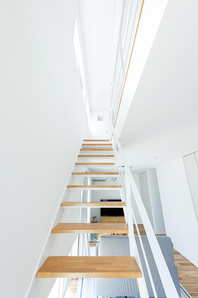 キッチン側から2階へと上がるスケルトン階段。光を映した真っ白な空間の中に、あたたかみのある木の質感がよく馴染んでいます。サンルームを兼ねた2階の階段ホールにたっぷりと陽が射し、階段を通じて家じゅうに光が広がります。