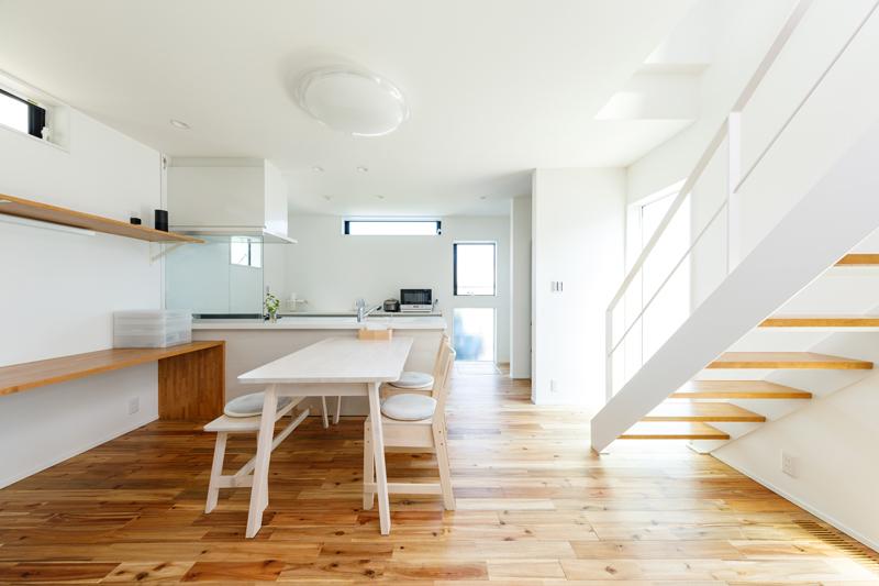 爽やかな淡色のクロスと木のぬくもりが調和したダイニングキッチン。空間になじむように、階段のスチール手摺も白で統一されています。色調の明るい木製のダイニングテーブルとチェア、ベンチを合わせました。