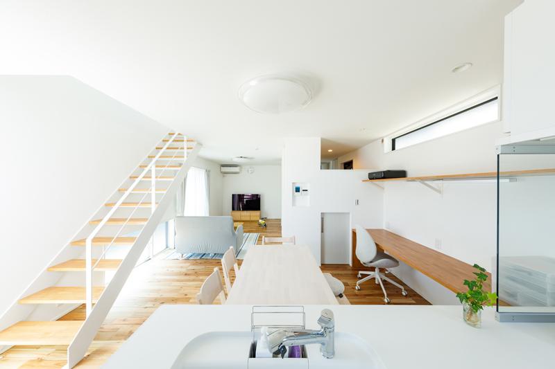 リビングまで広く見渡すことができるオープンキッチン。2階からスケルトン階段を伝って、やわらかな光が下りてきます。玄関の壁の一部を開いて光を通したり、視線が抜けるようにすることで、空間に奥行きを生み出しています。