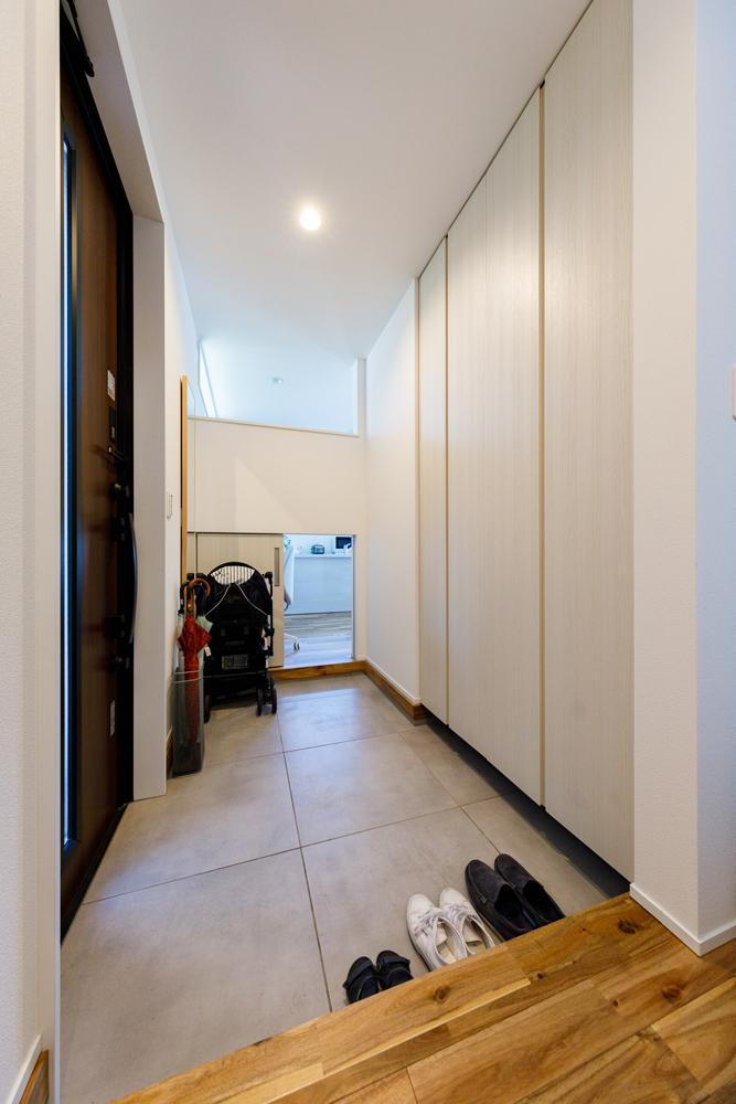家族が並んで靴を履ける広い玄関。正面には大型のクローゼット。さらにキッチン側の壁の上下を開いて動線をつくり、玄関に光を通すと同時に買い物帰りの荷物をキッチンへ運びやすくしています。