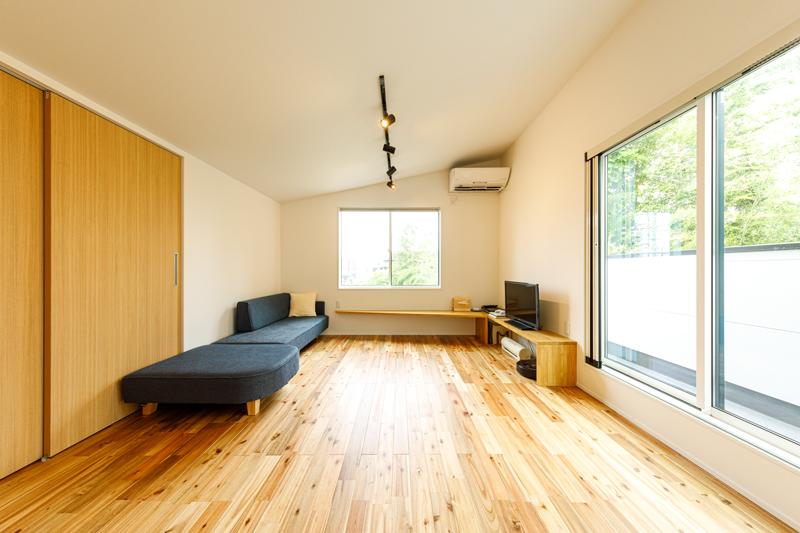 リビングの一角には造作のTVボード。立地や周辺環境に合わせて、ソファに体をあずけると窓の向こうに空と緑が広がるくつろぎをデザイン。フローリングには、木目が豊かなアカシアの無垢材を選びました。